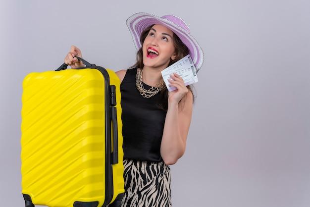 Gioiosa giovane viaggiatrice che indossa maglietta nera in cappello che tiene la valigia e biglietti sul muro bianco