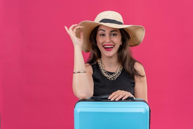 Gioiosa giovane viaggiatrice che indossa la maglietta nera in cappello mise la mano sul cappello sulla parete rossa