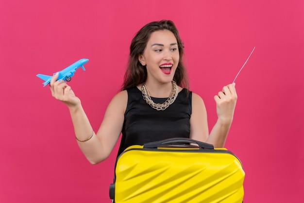 Радостная молодая женщина-путешественница в черной майке держит билет и играет с игрушечным самолетом на красной стене