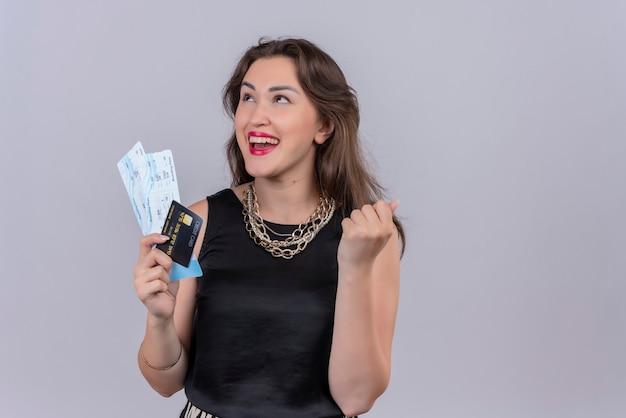 Gioiosa giovane donna che indossa la maglietta nera che tiene i biglietti e la carta di credito sulla parete bianca