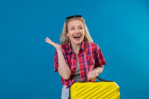 孤立した青い壁にスーツケースを保持している頭に赤いシャツと眼鏡を身に着けているうれしそうな若い女性旅行者