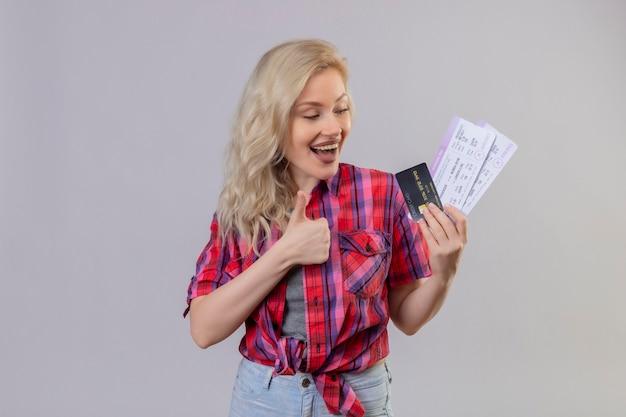 Gioiosa giovane donna che viaggia da indossare camicia rossa che tiene la carta di credito e biglietti il suo pollice in alto sulla parete bianca isolata