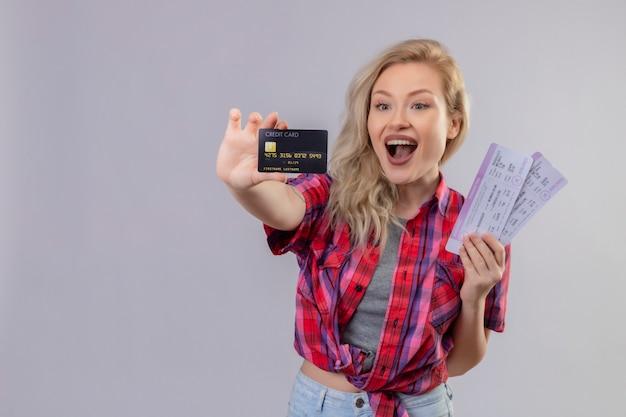 Gioiosa giovane viaggiatrice indossa camicia rossa che tiene carta di credito e biglietti sulla parete bianca isolata