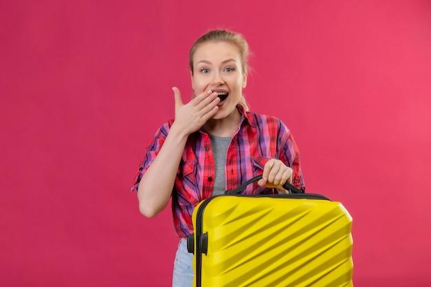 Gioiosa giovane viaggiatrice che indossa la camicia rossa che tiene la valigia coperta bocca sulla parete rosa isolata