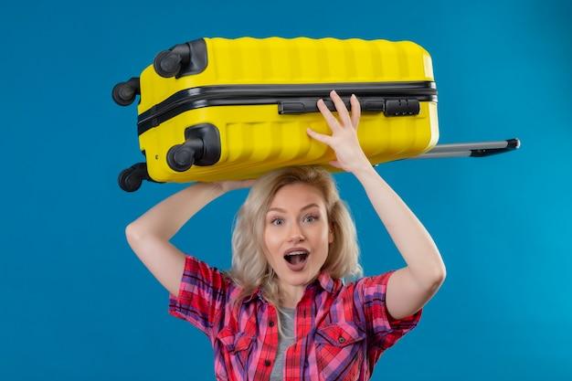 Gioiosa giovane viaggiatrice che indossa la camicia rossa che tiene la valigia sulla testa sulla parete blu isolata