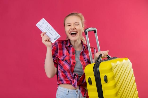 Gioiosa giovane donna che indossa la camicia rossa che tiene la valigia e il biglietto sul muro rosa isolato