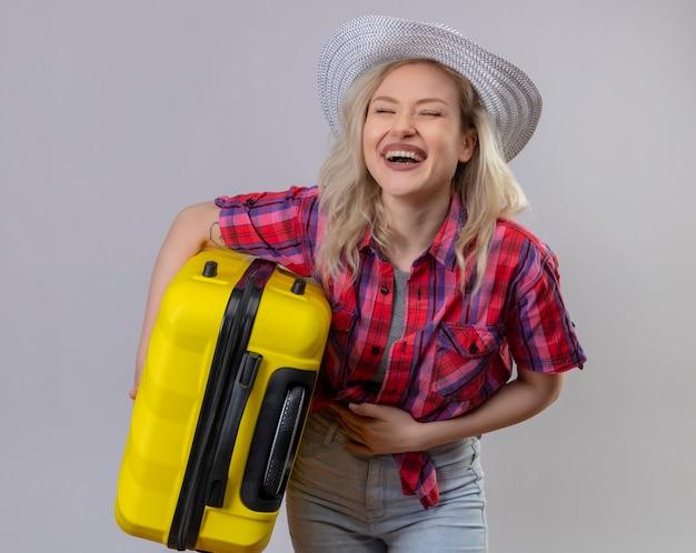Радостная молодая женщина-путешественница в красной рубашке в шляпе, держащая чемодан, положила руку на живот на изолированной белой стене