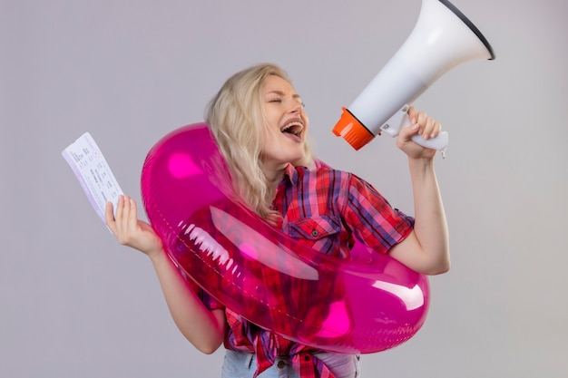 Радостная молодая женщина-путешественница в красной рубашке в надувном кольце держит билетных ораторов через громкоговорители на изолированной белой стене