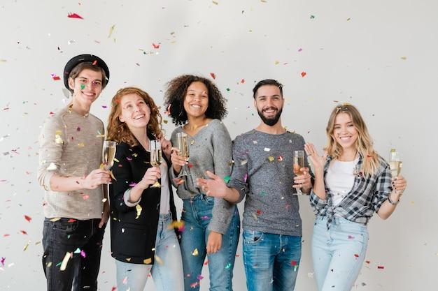 Веселые молодые друзья разных национальностей, стоящие в конфетти у белой стены, веселятся и тосты с шампанским на вечеринке