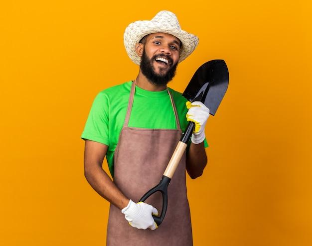Gioioso giovane giardiniere afro-americano che indossa cappello e guanti da giardinaggio che tengono la vanga isolata sul muro arancione