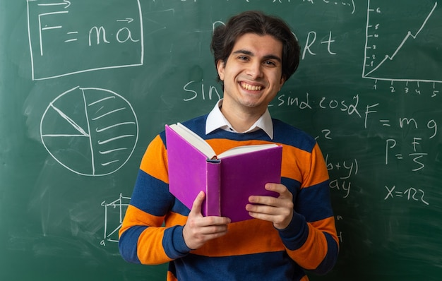 Gioioso giovane insegnante di geometria in piedi davanti alla lavagna in aula con in mano un libro guardando davanti