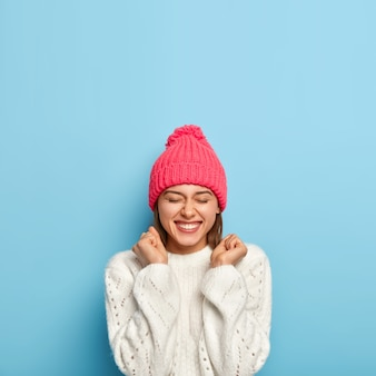 Joyful young girl feels overjoyed, raises clenched fists, being in good mood, wears white sweater and pink hat, dressed in warm clothes during cold autumn day, isolated on blue wall
