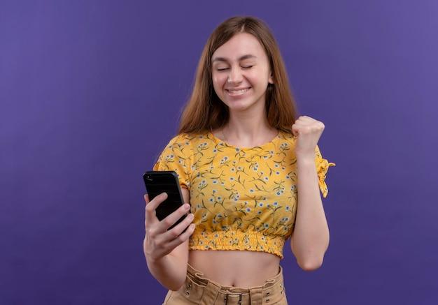 휴대 전화를 들고 복사 공간이 격리 된 보라색 공간에 주먹을 올리는 즐거운 어린 소녀