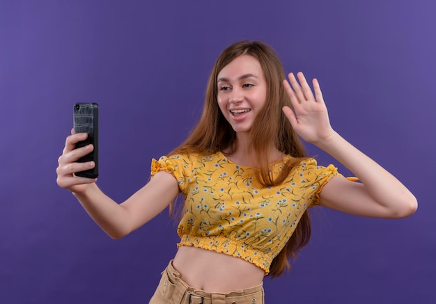 Ragazza allegra che tiene il telefono cellulare e che fa ciao gesto al telefono cellulare sullo spazio viola isolato