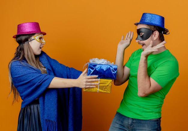 Joyful young girl in pink hat wearing masquerade eye mask holding gift boxes looking at surprised handsome man in blue hat wearing masquerade eye mask raising hands looking at boxes