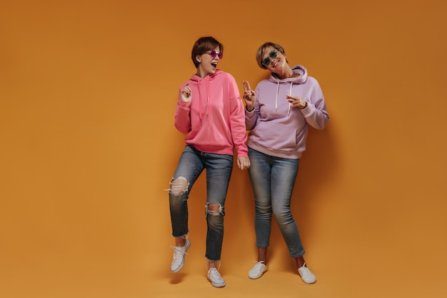 Joyful young girl in pink sweatshirt dancing with cool lady in lilac hoodie an green sunglasses on orange isolated backdrop.
