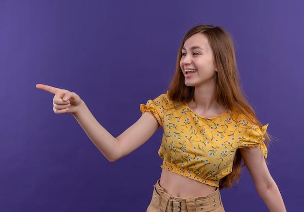 Радостная молодая девушка, указывая на левую сторону изолированного фиолетового пространства