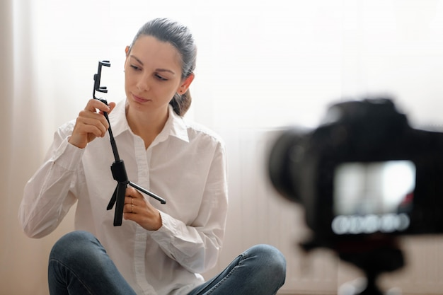 집에 앉아있는 동안 새로운 기술 장치에 대한 비디오 블로그 에피소드를 기록하는 즐거운 어린 소녀 프리미엄 사진