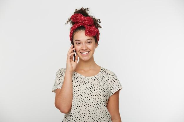 Gioiosa giovane ragazza che brilla di felicità, parlando con il suo fidanzato di miele sul telefono