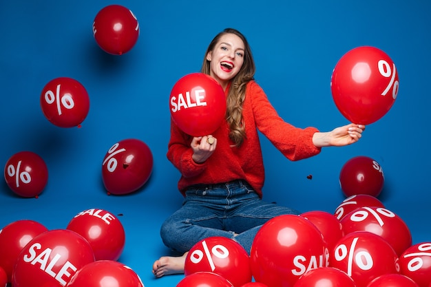 Joyful young girl sitting on the floor on blue  wall with red balloons, sale and discount concept