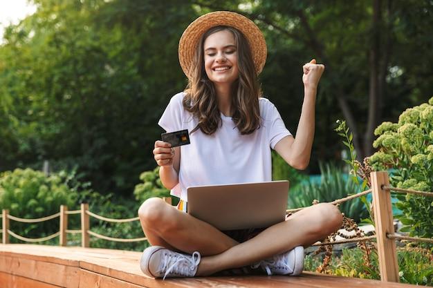 신용 카드를 들고 야외 공원에서 노트북 컴퓨터와 함께 앉아 즐거운 어린 소녀