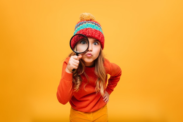 Joyful young girl in sweater and hat looking at the camera with magnifier over orange