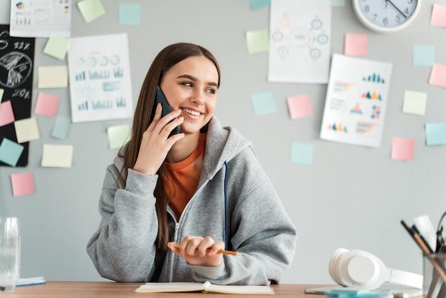 스티커와 함께 벽의 배경에 전화 통화하는 즐거운, 어린 소녀. 연구에 긍정적 인 학생.