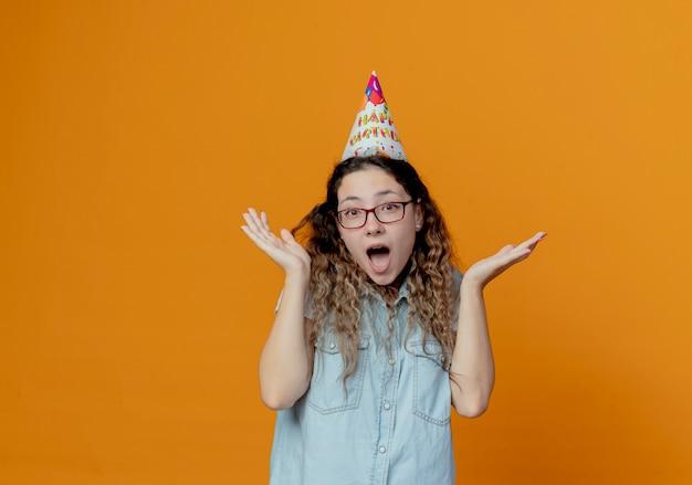 안경과 생일 모자를 쓰고 즐거운 어린 소녀가 오렌지 배경에 고립 된 손을 펼칩니다.