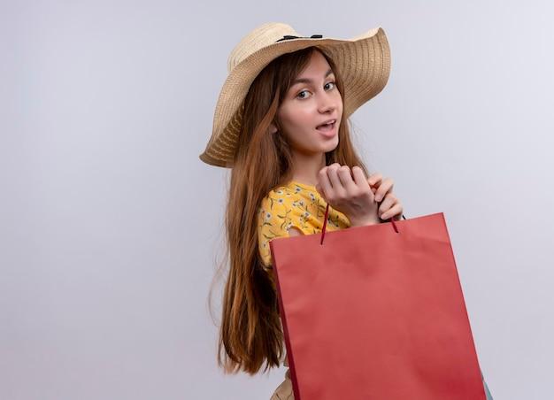 コピースペースと孤立した白いスペースに紙袋を保持している帽子をかぶってうれしそうな少女