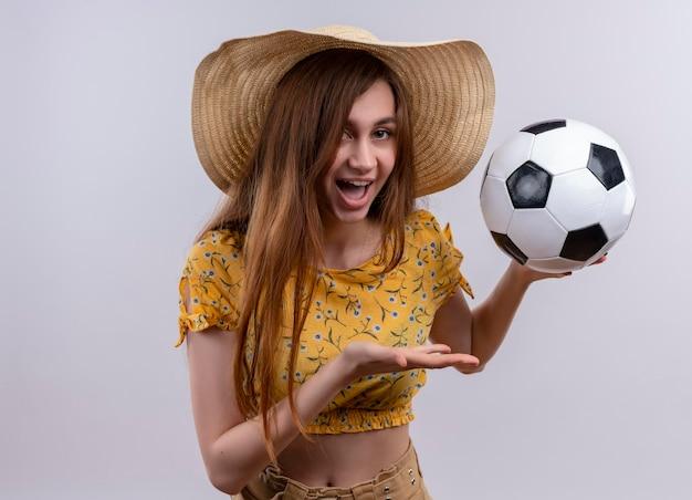 孤立した白いスペースでサッカーボールを保持している帽子をかぶってうれしそうな少女
