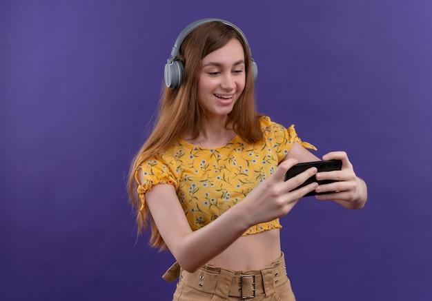 헤드폰을 착용하고 복사 공간이 격리 된 보라색 공간에 휴대 전화를 들고 즐거운 어린 소녀