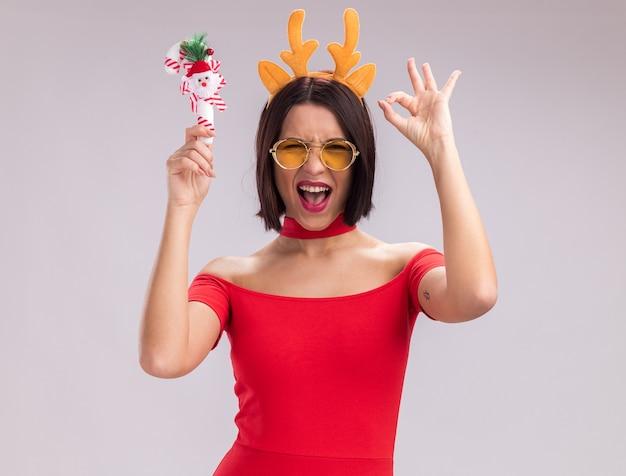 Радостная молодая девушка в головной повязке с оленьими рогами и очках, поднимающая рождественский орнамент из леденцов, глядя в камеру, делает знак ок, изолированные на белом фоне