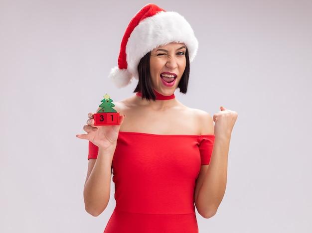 Радостная молодая девушка в шляпе санта-клауса держит елочную игрушку с датой, глядя в камеру, подмигивая, делая жест да, изолированные на белом фоне