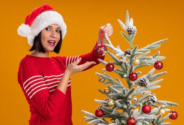 Радостная молодая девушка в шляпе санта-клауса, стоящая в профиль возле елки, украшающая ее рождественскими шарами, смотрит в камеру, указывая на безделушку, изолированную на оранжевом фоне