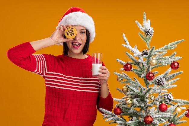 Gioiosa giovane ragazza che indossa il cappello di babbo natale in piedi vicino all'albero di natale decorato con un bicchiere di latte e biscotti davanti all'occhio guardando la telecamera isolata su sfondo arancione