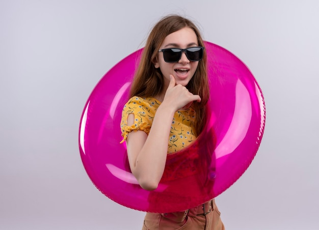 Gioiosa ragazza giovane indossando occhiali da sole e anello di nuotata mettendo la mano sul mento su uno spazio bianco isolato con spazio di copia