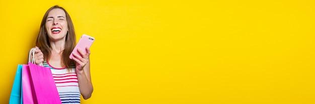 노란색 배경에 쇼핑백을 들고 전화를 들고 즐거운 어린 소녀. 배너.
