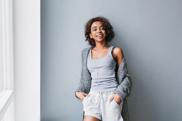 Joyful young girl with short curly hair standing next to gray wall and big white window. wearing casual home clothes, gray cardigan, shirt, shorts, long stylish necklace.