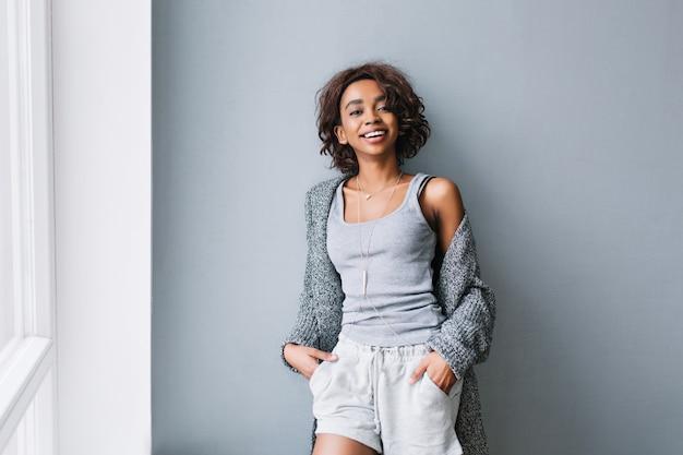 Gioiosa ragazza con i capelli ricci corti in piedi accanto al muro grigio e grande finestra bianca. indossare abiti casual per la casa, cardigan grigio, camicia, pantaloncini, collana lunga ed elegante.
