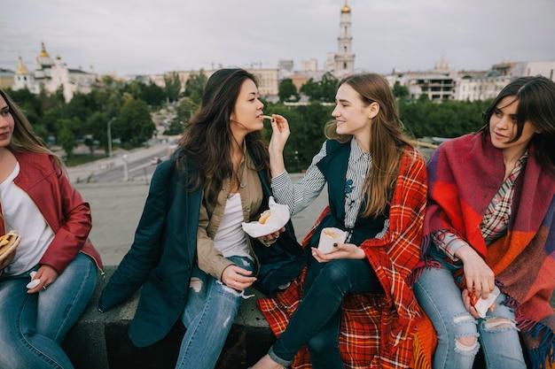 함께 좋은 시간을 보내는 즐거운 어린 소녀. 지붕에 카페에서 감자 튀김을 공유하는 가까운 친구. 휴식과 오락을위한 특이한 장소, 쾌활한 분위기 컨셉의 여가