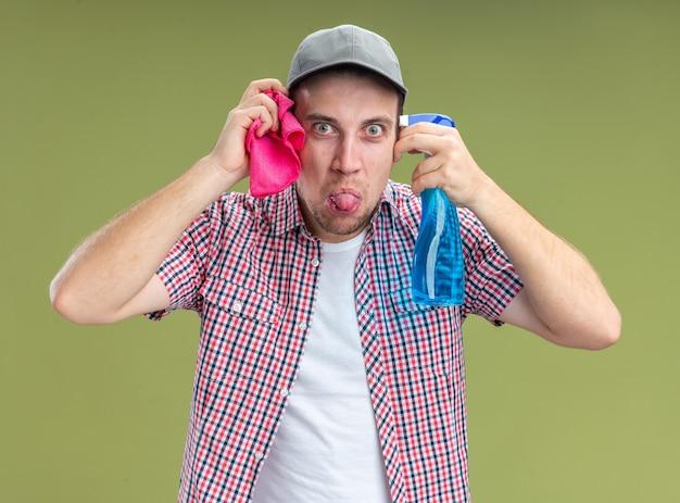 オリーブグリーンの壁に分離された舌を示す顔の周りのぼろきれで洗浄剤を保持しているキャップを身に着けているうれしそうな若い男クリーナー