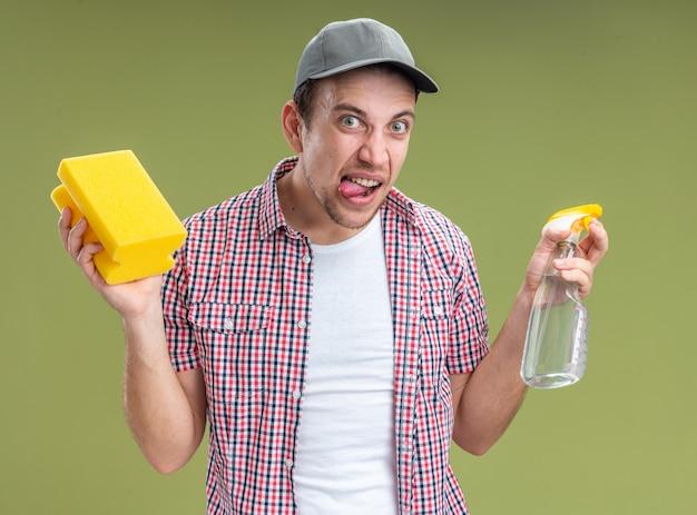 オリーブグリーンの背景に分離されたスポンジと洗浄剤を保持しているキャップを身に着けているうれしそうな若い男クリーナー