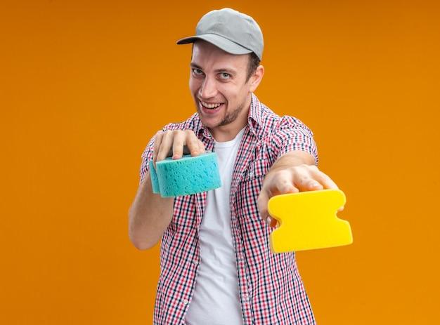 Gioioso giovane pulitore che indossa un cappuccio che tiene fuori le spugne per la pulizia alla telecamera isolata su sfondo arancione