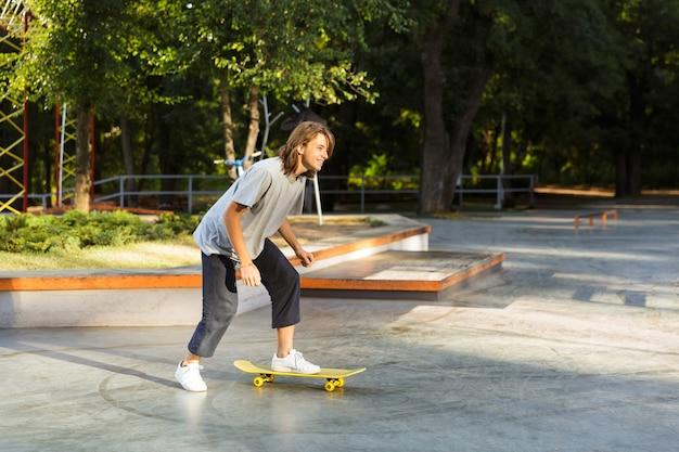 Joyful young guy spending time at the skate park, riding on a skateboard