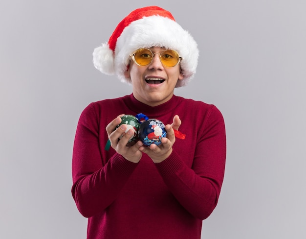 흰색 배경에 고립 된 크리스마스 트리 볼을 들고 안경 크리스마스 모자를 쓰고 즐거운 젊은 남자