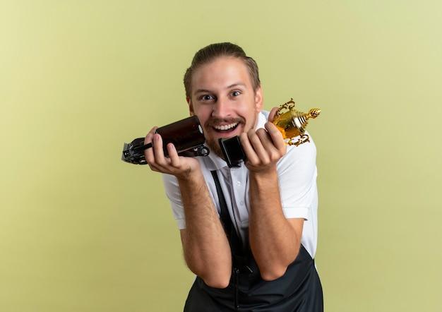 머리 가위, 스프레이 병 및 우승자 컵을 들고 즐거운 젊은 잘 생긴 이발사 올리브 그린에 고립