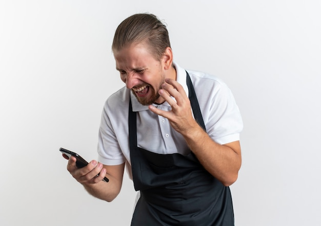 Радостный молодой красивый парикмахер в униформе держит и смотрит на мобильный телефон, держа руку на воздухе, изолированную на белом