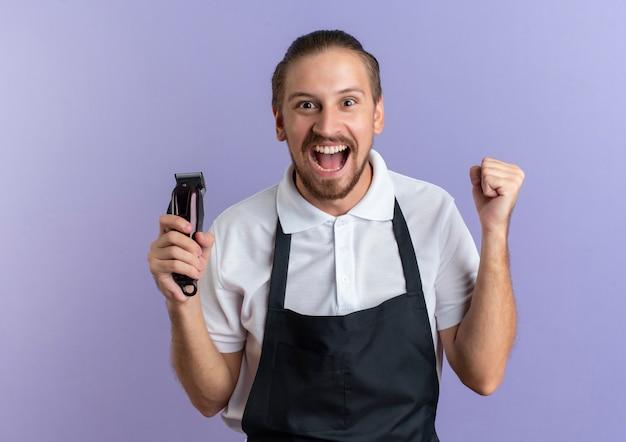 Gioioso giovane barbiere bello che indossa uniforme che tiene i tagliacapelli e il pugno di serraggio isolato sulla porpora