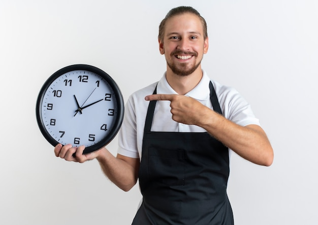 Gioioso giovane barbiere bello che indossa la tenuta uniforme e indicando l'orologio isolato su bianco