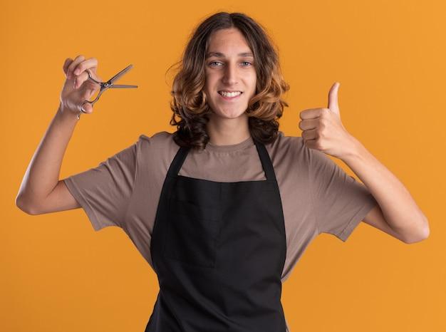 Gioioso giovane barbiere bello che indossa un'uniforme che tiene le forbici guardando la parte anteriore che mostra il pollice in alto isolato sulla parete arancione